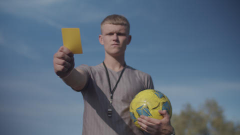 Soccer referee with yellow card warning player Live Action