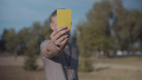 Soccer referee showing yellow card on the pitch Live Action