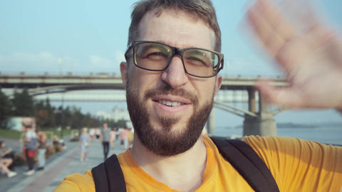 Happy male blogger with glasses and with a beard speaks to the camera on the Live Action
