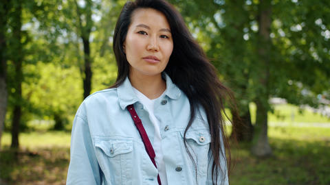 Serious Asian lady standing outdoors in green park looking at camera Footage