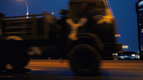 A convoy of military equipment rides through the city at night with headlights Footage