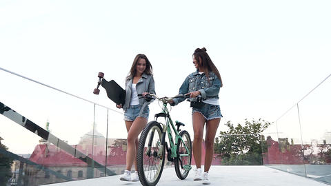 Pretty cheerful young ladies in fashion clothes walking with bicycle and Footage