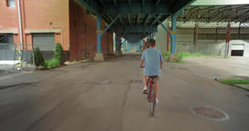 Following Biker Under Bridge in City Industrial Area Footage