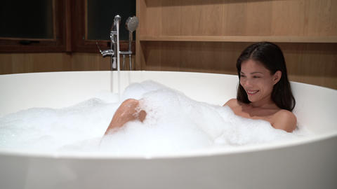 Beautiful Woman enjoying relaxing bubble bath lifestyle real natural body care Live Action