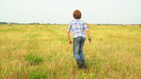 Boy teenager running away on autumn field in countryside. Back view teenager boy Live Action