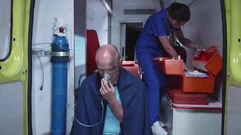 Sick man sit in oxygen mask in ambulance car Live Action