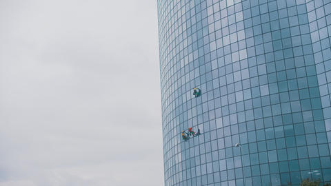 Three men workers hanging on ropes by the exterior blue windows of a business Live Action