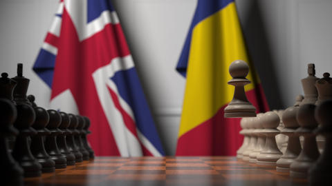 Flags of Great Britain and Romania behind pawns on the chessboard. Chess game or Live Action