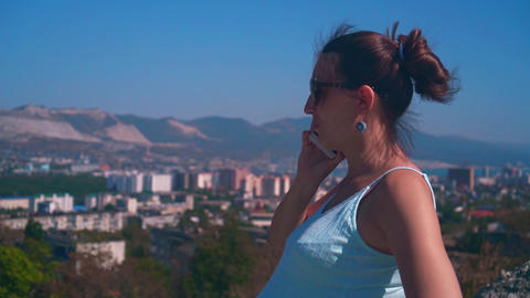 Young attractive woman in glasses and a blue dress on the background of the city Footage