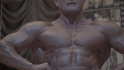 Male bodybuilder shows the muscles of the body Footage