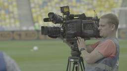 Cameraman with a camera on a tripod takes the news on the stadium Footage