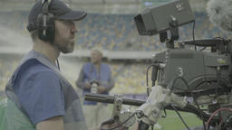 Cameraman with a camera shoots a TV broadcast at the stadium Footage