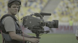 Cameraman with a camera on the Steadicam at the stadium before the TV broadcast Footage