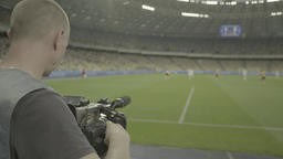 The cameraman shoots a football match at the stadium Footage