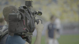 Cameraman with a camera at the time of the TV broadcast of the match at the stad Footage