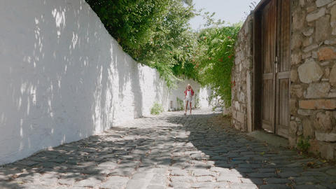 Girl walking on narrow street in old city. Tourist girl walking on sunny street Live Action