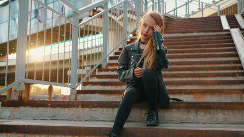 Lonely girl in black leather jacket sitting on stairs at sunshine background Footage