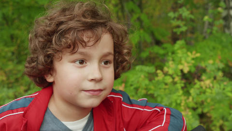 Portrait curly brunette boy in summer park. Close up face teenager boy on Live Action