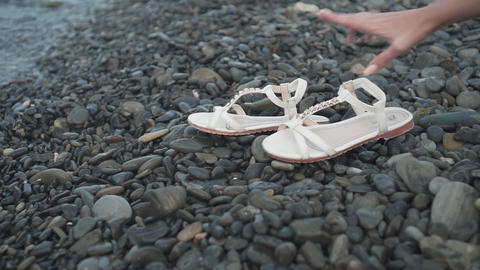 White sandals on a rocky and wet seashore. Woman's hand takes sandals Footage
