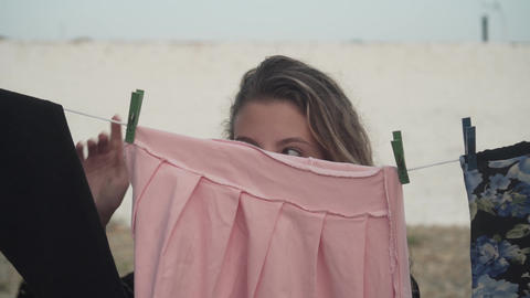 A young girl steals a pink dress, removing it from clothespins, which are dried Live Action