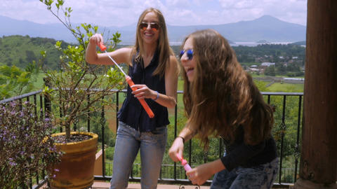 Three teens laughing and playing outside with bubbles and with mountains in the Footage