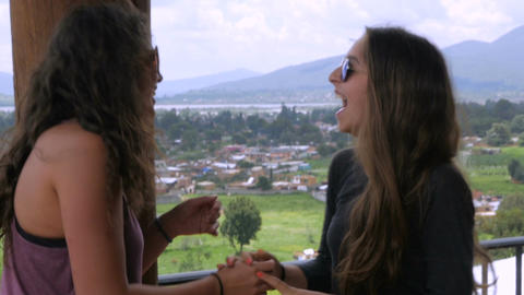 Three attractive teenage girls with long hair and sunglasses laughing in slow mo Live Action