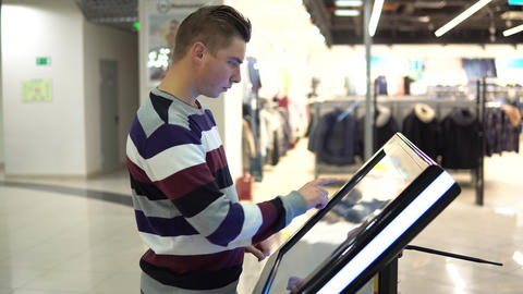 A young man is watching a navigation map on an electronic touch table in a Live Action