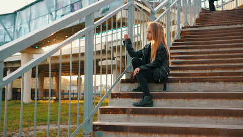 Pensive teenage girl in leather jacket sitting on stairs Footage
