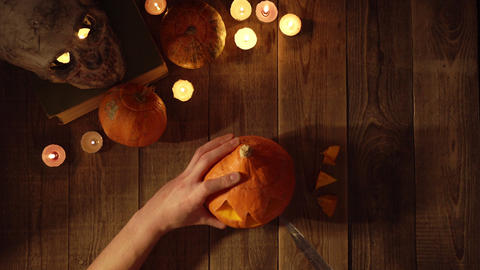 Man carves from a pumpkin Jack-o-lantern on wood table timelapse top view Footage