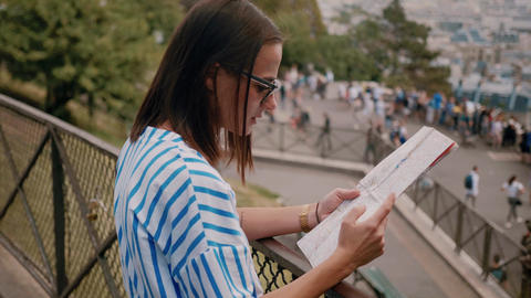 Young woman in Paris checks destinations on the map Live Action
