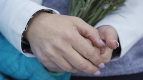 Close-up of female middle-aged hands holding the hand of a young girl. Older Footage