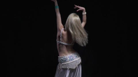 View from the back, on a slim woman dancing with her hands up Live Action
