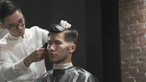Barber dries asian client with hairdryer Live Action