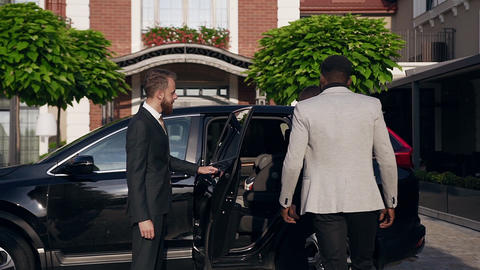 Back view of attractive business people going to the black vehicle while driver Footage