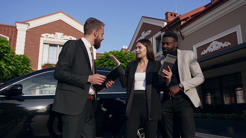 Team of three young mixed-race office workers using tablet computer and worker Live Action