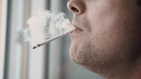man smokes a cigarette at home GIF