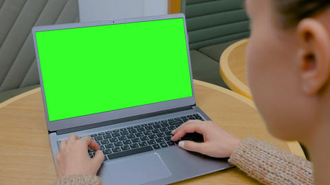 Woman looking at laptop computer with blank green screen in cafe Live Action