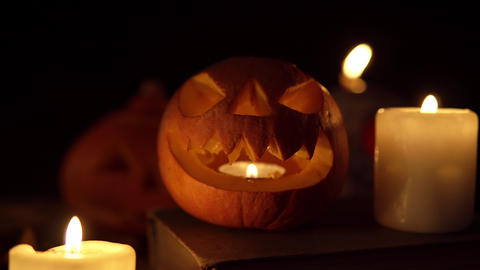One little Jack pumpkin with sharp teeth and evil eyes stands on an old book in Live Action