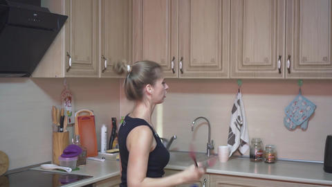 Beautiful girl in the kitchen. The blonde is having fun in the kitchen, having Live Action