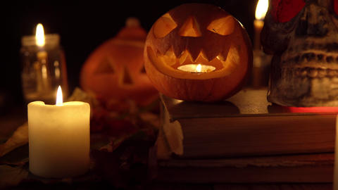 Scary toothy pumpkin Jack next to skull on old books in candlelight Live Action