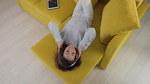Top view of relaxing gorgeous cheerful woman with headphones laying on the cozy Footage