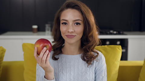 Close up of splendid cheerful lady eating red fresh apple and looking at camera Footage