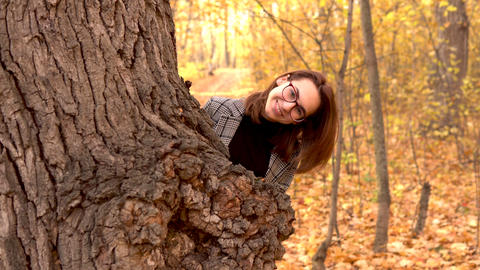A young woman in glasses hides behind a large tree of leaves in the autumn Live Action