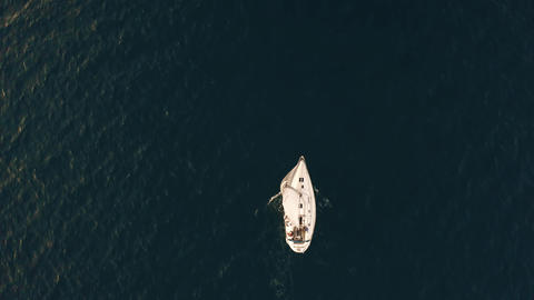 Aerial top down shot of unknown people travelling on a yacht at sea Live Action