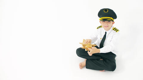 Boy in pilot's uniform plays with generic wooden toy plane Live Action