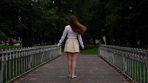 Young woman stand on footbridge and turn back with hurt emotion, slow motion Live Action