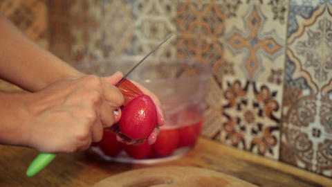 Female hands peeling boiled tomatoes in kitchen Live Action