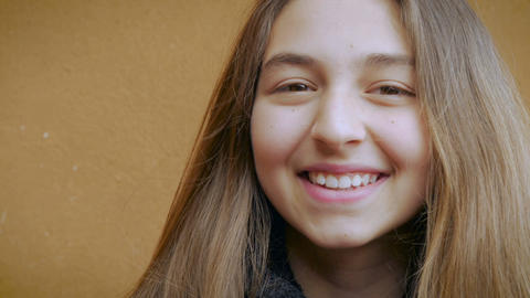 Portrait of a young attractive teenage girl smiling and waiving at the camera Footage