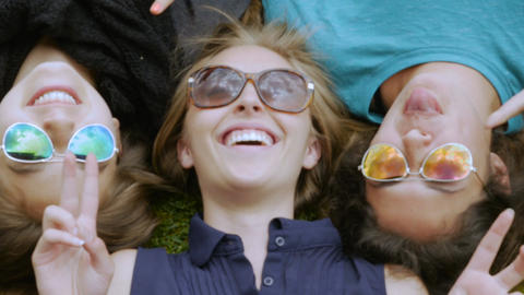 Three teenage girls lying in the grass making silly faces to the camera while we Footage