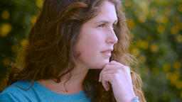 A young woman with long brown hair looks off in the distance thinking with her h Footage